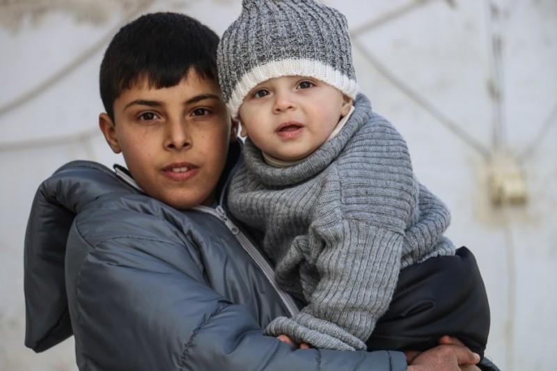 Abdulrahman, 12, nosi na rękach swojego brata.