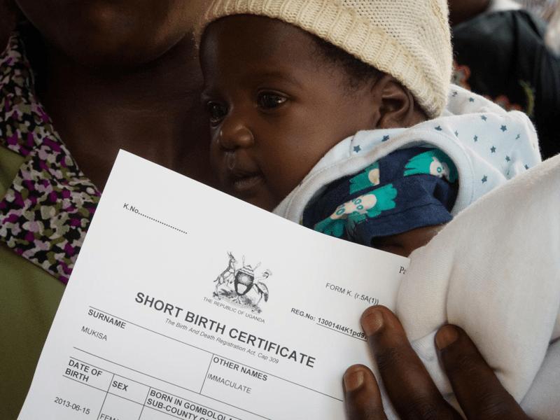 Mama trzyma w ręku skrócony akt urodzenia wygenerowany dzięki Mobile Vital Records System (Mobile VRS). Szpital Mulago w Kampali.
