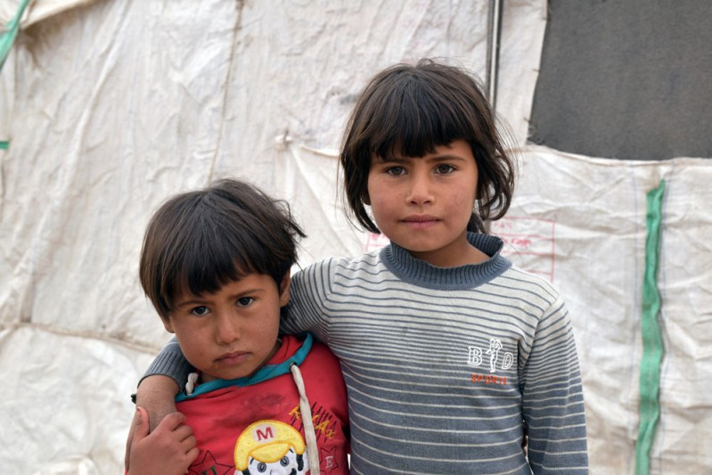 8. Haya, 3, (left) and Sabeen, 5, (right) outside the shelter where they live