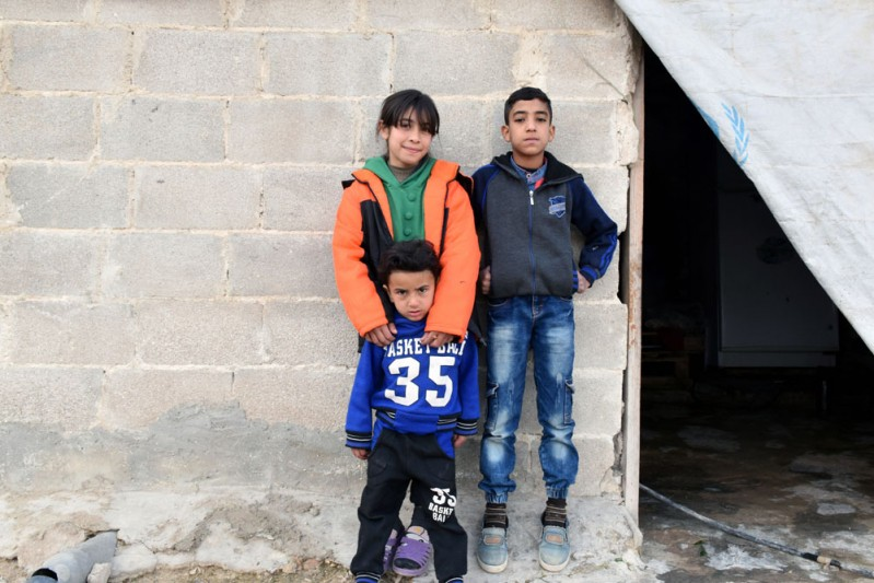 21. Yasser, 11, (right) stands with his siblings outside the family home in Hasiyah
